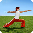 Woman wearing red pants is doing yoga outside.